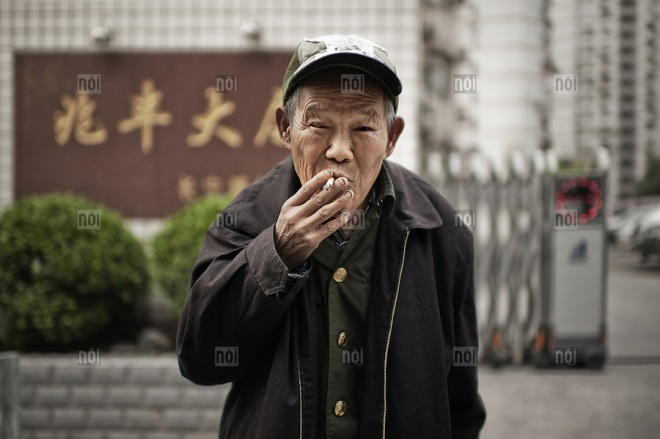Blind old man smoking a cigarette in a street of Shanghai, China