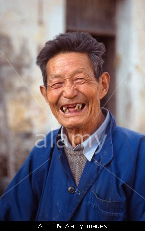 Old man with crooked and missing teeth in the 11th century village of Xidi, Anhui Province China