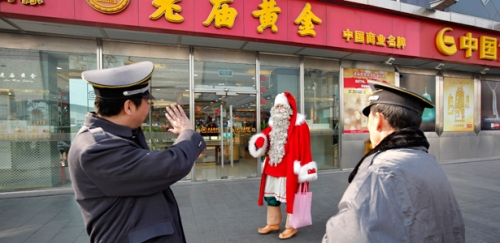 A man dressed as Santa Claus walks past two security guards in downtown Shanghai December 23, 2010. Officially recognized by the Finland government after a four-year training, the man is one of 50 officially registered Santa Clauses who is paying a visit to Shanghai, warming up the Christmas holidays. REUTERS/Aly Song (CHINA - Tags: SOCIETY IMAGES OF THE DAY)